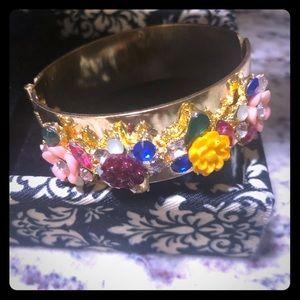 A hinged goldtone flower and crystal bracelet